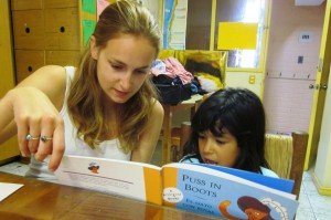 VE Global Volunteer reading with child.